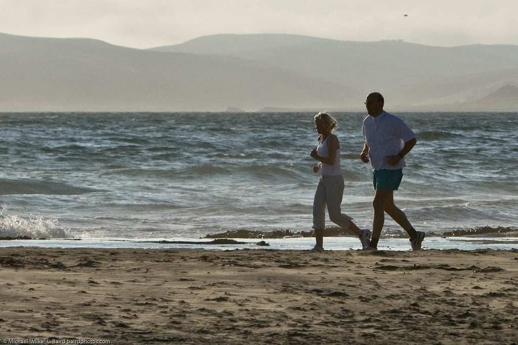 A couple is running in a beach